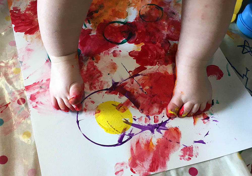 Close up of a baby using their feet to paint onto a piece of paper